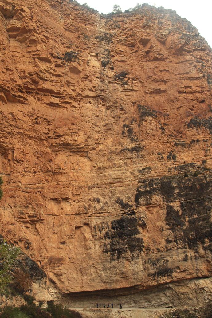 Personas minúsculas en la pared de la montaña